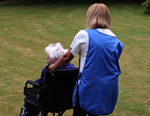 Old lady in wheelchair with carer